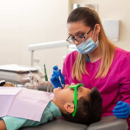 Young boy laying in a treatment chair wearing green glasses, while a dental hygienist is examining his mouth