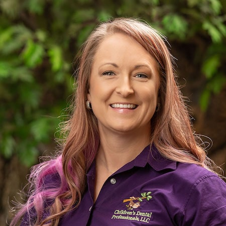 Barb our dental hygienists wearing a purple top with long brown and pink hair