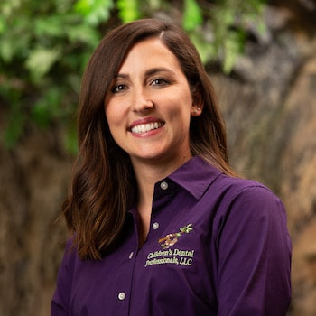 Brooke our marketing coordinator wearing a purple top, with long brown hair and smiling