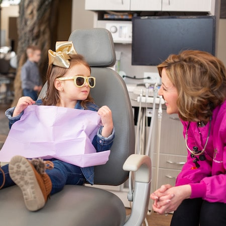 Young patient in a dental chair wearing yellow sun glasses and a purple bib