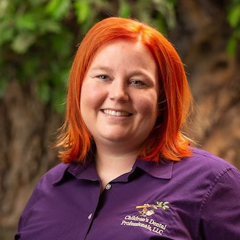 Christy our dental assistant wearing a purple top, with orange shoulder length hair and smiling