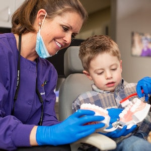 Dr. Frazier helping a patient learn how to brush their teeth correctly