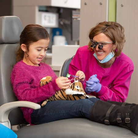 Young girl sitting in dental chair practicing how to floss on a toy tiger