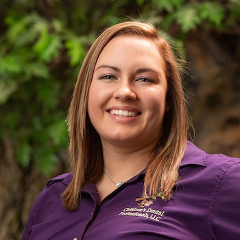 Megan R our Dental Hygienist wearing her purple dental uniform