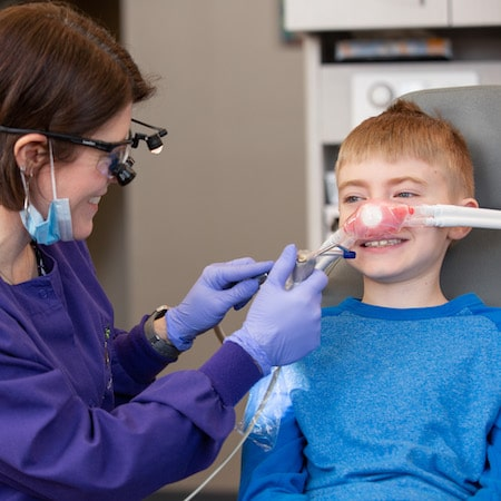 Dr. Walker in the dental office with a child who is being sedated with Nitrous Oxide