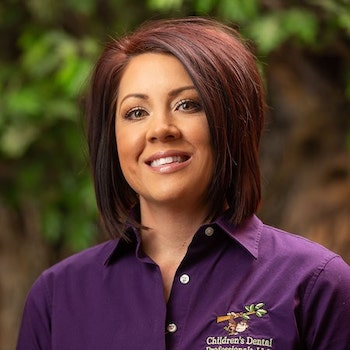 Summer our dental assistant wearing a purple top, with short brown hair and smiling