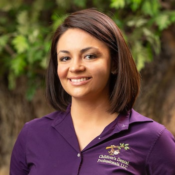 Taylor our dental hygienists wearing a purple top, with short brown hair and smiling