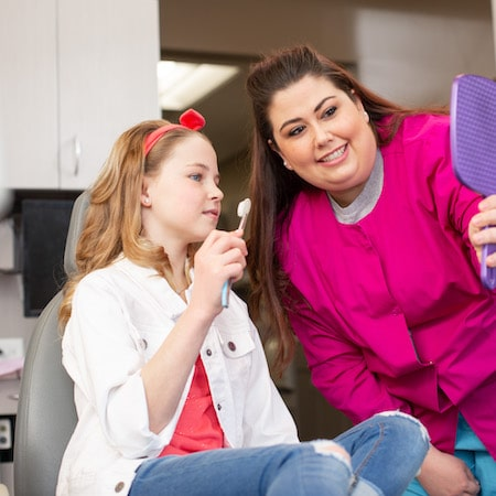 Young girl holding a toothbrush looking in a mirror that a dental hygienist is holding