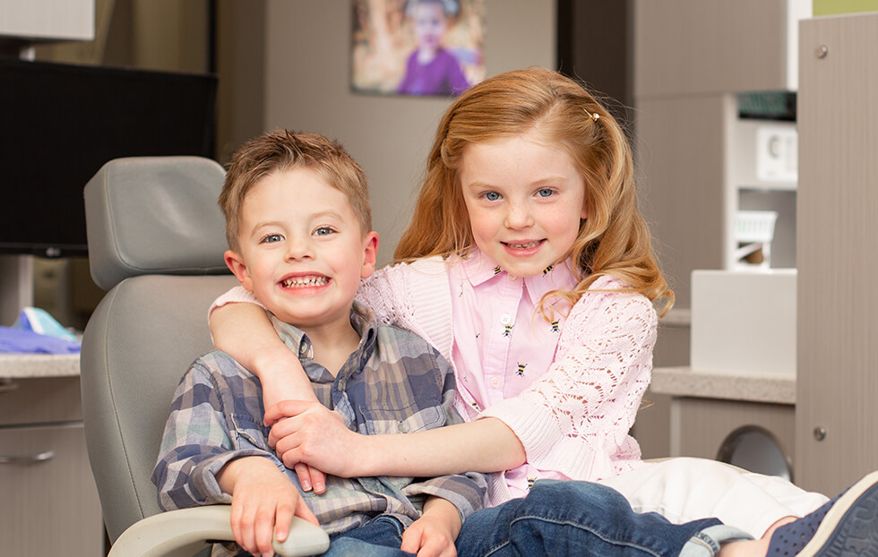 Two children sat in the dentist chair and hugging