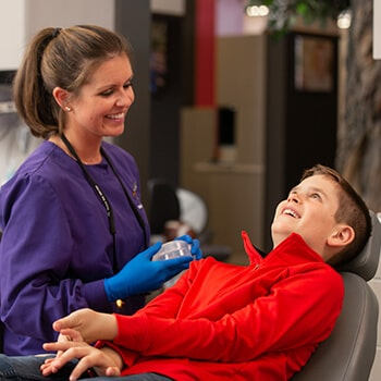 A child laughing inside the dental office while lying in the dentist's chair and next to him is the doctor showing him a container while wearing blue gloves