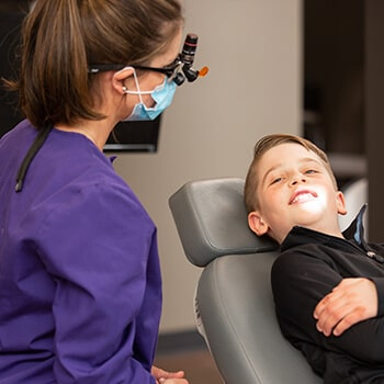 The doctor inside the office with a child who is lying in the dentist's chair smiling while pointing a light on his teeth