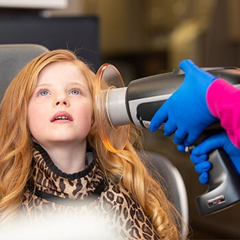 A little red-haired girl in the dental office dentist's chair looking up while the dentist approaches an appliance to check her teeth