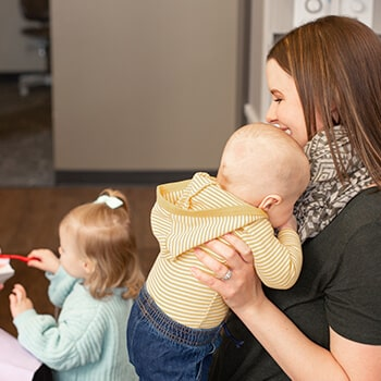 A woman inside the dental office hugging a baby while in the background she sees a little girl playing with a toothbrush