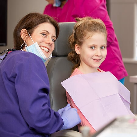 Dr. Walker inside the dental office next to a girl who is sitting in the dentist's chair, both smile in front