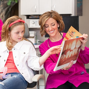 Dr. Parr showing a book about dental care to a girl who is sitting in the dentist's chair wearing a red ribbon on her head