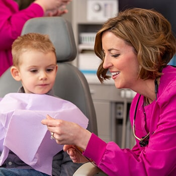 Dr. Parr with a child patient inside the dental office while showing her a toothbrush
