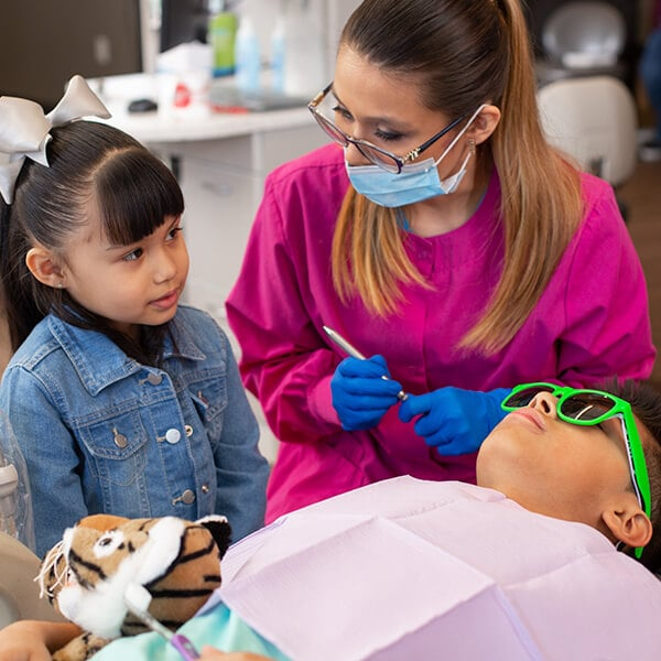 One of our dental assistants wearing a mouth cover while talking with a little girl who is standing and a boy is lying on the side of the dentist chair wearing green glasses