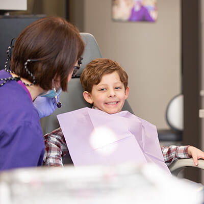 Dr. Walker talking to a little boy who is smiling in the dentist's chair with a handkerchief on his chest