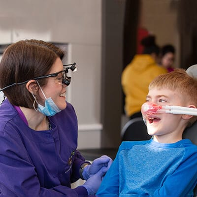 Dr. Walker talking to a child who is sitting in the dentist's chair and wearing a sedation mask while laughing