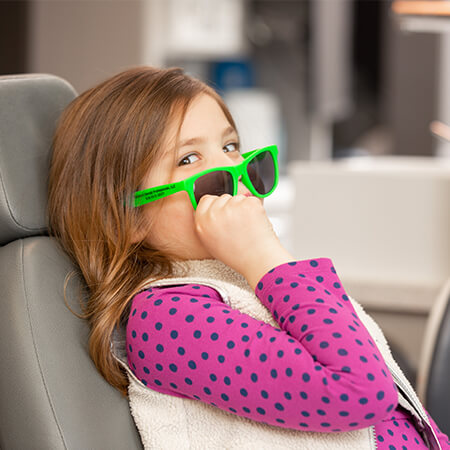 A small girl with long brown hair putting on green glasses while sitting in the dentist's chair